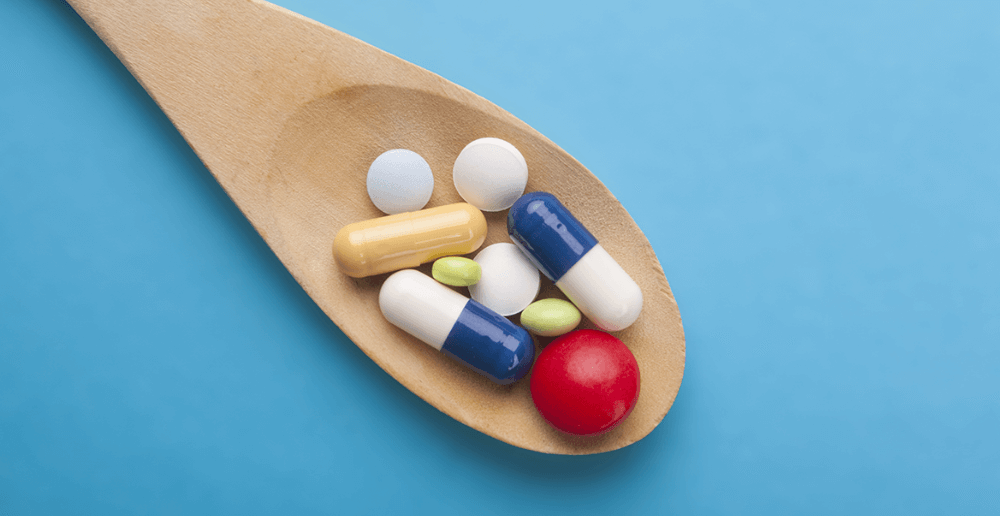 Photo of pills, tablets and capsules on a wooden spoon.