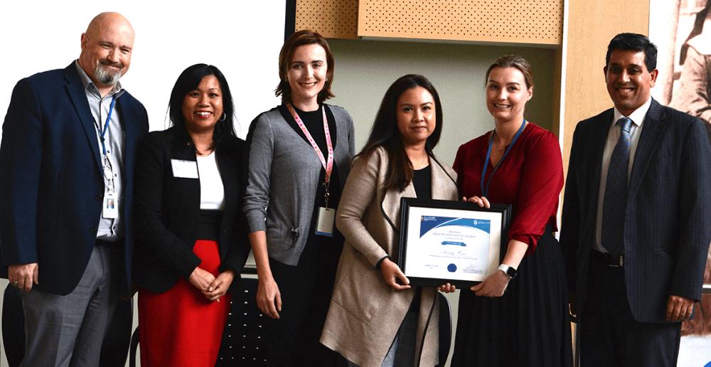 Gina Trinidad, Chef des opérations en santé de l'ORSW (deuxième de la gauche) présente le prix d'innovation en santé à Greg Reid, Renae Reiser, Diana Alvaran, Stefanie Turner et Vikas Sethi, tous membres de l'équipe Votre chez-vous - Notre priorité.