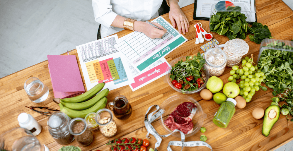 Photo of a dietitian sitting at a table filled with healthy food